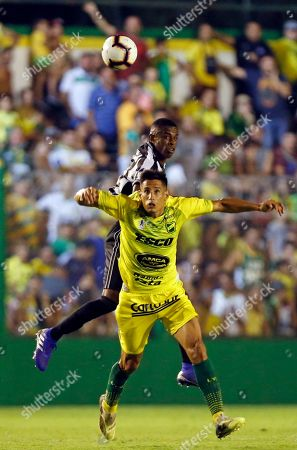 Marcelo Benvenuto, top, of Brazil's Botafogo, fights for the ball with Fernando Marquez of Argentina's Defensa y Justicia during a Copa Sudamericana soccer game in Florencio Varela, on the outskirts of Buenos Aires, Argentina
