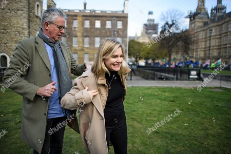 A journalist helps Justine Greening MP to put on her jacket, after speaking to media in Westminster, London. Conservative and Labour MPs have resigned form their respective parties. and joined newly formed The Independent Group, a breakaway campaign group formed by seven defecting Labour MPs.