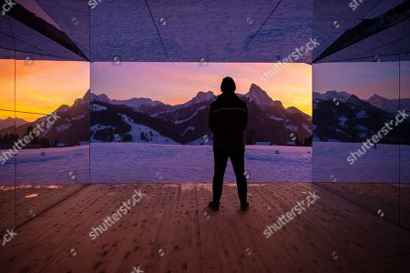 A man visits the latest installation entitled 'Mirage Gstaad' by American artist Doug Aitken at Gstaad, Switzerland, 20 February 2019 (issued 21 February 2019). This structure, presented during the exposition 'Elevation 1049: Frequencies', will be visible for the next two years.