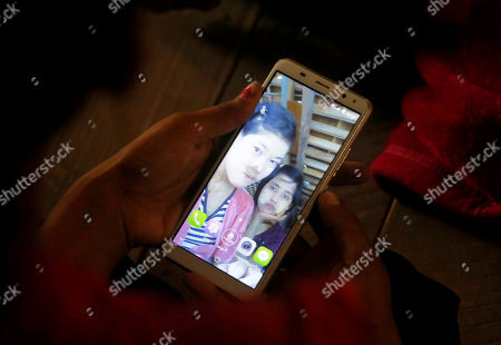The elder sister of Ni Ni Soe looks at the phone screen with the photo of her sister at the MyinPhyu village in Buthidaung Township, northern Rakhine State, western Myanmar, 21 February 2019. Ni Ni Soe, an 18-year-old girl from the village, was killed in the fight between the Myanmar military and the Arakan Army (AA) on 20 February 2019 near MyinPyu village. Villagers said Heavy weapons and bullets hit the houses in the village during the clash. According to the United Nations (UN), 4,500 residents fled from village shelters into temporary camps in Ponnagyun, Buthidaung, Rathetaung and Kyauktaw townships, as fighting continues between Myanmar military troops and the Arakan Army in northern Rakhine State. The Arakan Army, which was founded in 2009, has not taken part in the National Ceasefire Agreement (NCA).