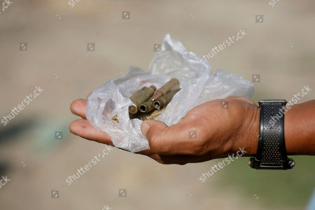 Stock Photo of A villager shows bullets that was left after the fight at MyinPhyu village in Buthidaung Township, northern Rakhine State, western Myanmar, 21 February 2019. Ni Ni Soe, an 18-year-old girl from the village, was killed in the fight between the Myanmar military and the Arakan Army (AA) on 20 February 2019 near MyinPyu village. Villagers said heavy weapons and bullets hit the houses in the village during the clash. According to the United Nations (UN), 4,500 residents fled from village shelters into temporary camps in Ponnagyun, Buthidaung, Rathetaung and Kyauktaw townships, as fighting continues between Myanmar military troops and the Arakan Army in northern Rakhine State. The Arakan Army, which was founded in 2009, has not taken part in the National Ceasefire Agreement (NCA).
