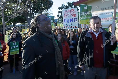 Oakland Education Association President Keith Brown, center left, yells after speaking outside of Manzanita Community School in Oakland, Calif., . Teachers in Oakland, California, went on strike Thursday in the country's latest walkout by educators over classroom conditions and pay