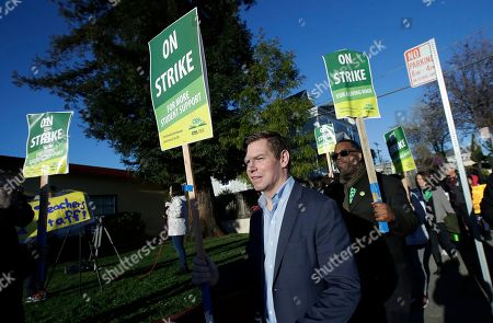 Rep. Eric Swalwell, D-Calif., center, marches with Oakland Education Association President Keith Brown, center right, along with teachers and supporters outside of Manzanita Community School in Oakland, Calif., . Teachers in Oakland, California, went on strike Thursday in the country's latest walkout by educators over classroom conditions and pay