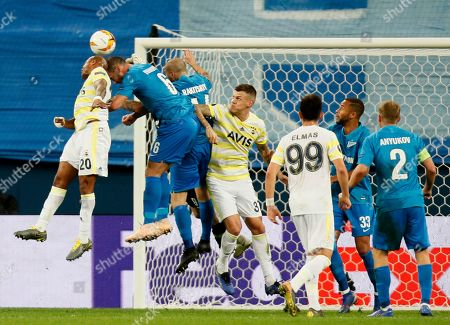 Fenerbahce's Andre Ayew, left, and Zenit's Branislav Ivanovic jum for the ball during the Europa League round of 32 soccer match between Zenit St.Petersburg and Fenerbahce at the Saint Petersburg Stadium in St.Petersburg