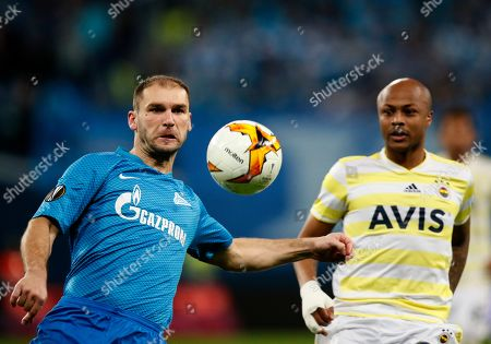 Zenit's Branislav Ivanovic, left, and Fenerbahce's Andre Ayew challenge for the ball during the Europa League round of 32 soccer match between Zenit St.Petersburg and Fenerbahce at the Saint Petersburg Stadium in St.Petersburg