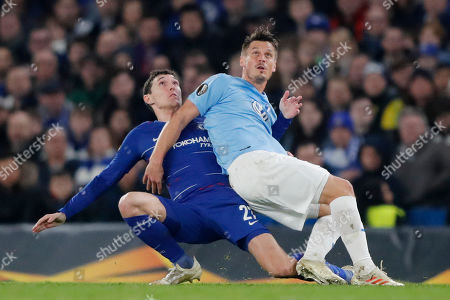 Chelsea's Andreas Christensen, left, and Malmo's Markus Rosenberg fall as they vie for the ball during the round of 32, second leg, Europa League soccer match between Chelsea and Malmo FF at Stamford Bridge stadium in London