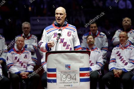 Mark Messier gestures to fans while speaking during a pregame ceremony to acknowledge the 1994 Rangers before an NHL hockey game between the New York Rangers and the Carolina Hurricanes, in New York