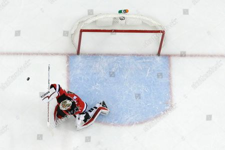 New Jersey Devils goaltender Keith Kinkaid blocks a shot from the Pittsburgh Penguins during the first period of an NHL hockey game, in Newark, N.J. The Penguins won 4-3