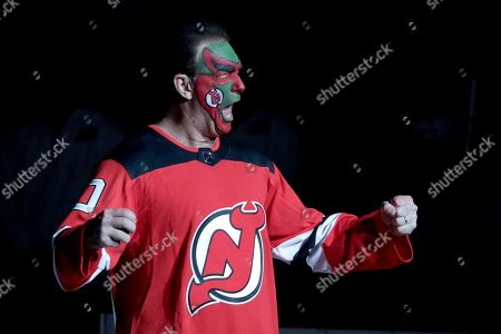 Actor Patrick Warburton, center, is dressed as Seinfeld cast member David Puddy, while walking up to center ice for the ceremonial puck drop prior to an NHL hockey game between the New Jersey Devils and the Pittsburgh Penguins, in Newark, N.J