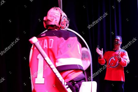 Actor Patrick Warburton, right, dressed as Seinfeld cast member David Puddy, greets New Jersey Devils goaltender Keith Kinkaid (1) as he heads to the ice for warmups prior to an NHL hockey game against the Pittsburgh Penguins, in Newark, N.J. The Penguins won 4-3