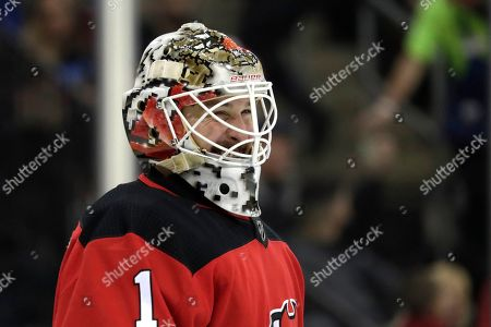 New Jersey Devils goaltender Keith Kinkaid reacts between plays against the Pittsburgh Penguins during the first period of an NHL hockey game, in Newark, N.J