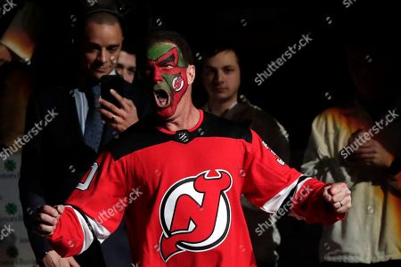 Stock Picture of Actor Patrick Warburton, center, is dressed as Seinfeld cast member David Puddy, while walking up to center ice for the ceremonial puck drop prior to an NHL hockey game between the New Jersey Devils and the Pittsburgh Penguins, in Newark, N.J