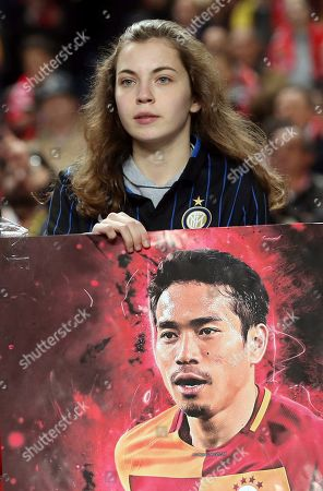 A fan holds a picture of Galatasaray's Yuto Nagatomo during the Europa League round of 32, second leg, soccer match between Benfica and Galatasaray at the Luz stadium in Lisbon