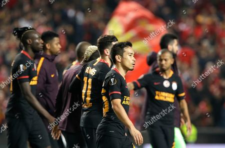 Galatasaray's Yuto Nagatomo, foreground, and his teammates leave the field at the end of the Europa League round of 32, second leg, soccer match between Benfica and Galatasaray at the Luz stadium in Lisbon, . The game ended in a 0-0 draw and Benfica advances after winning the first leg 2-1