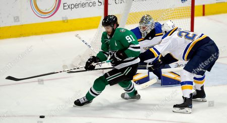Dallas Stars center Tyler Seguin (91) attempts to gain control of the puck as St. Louis Blues defenseman Vince Dunn (29) helps goaltender Jordan Binnington, rear, defend against the pressure during an NHL hockey game in Dallas