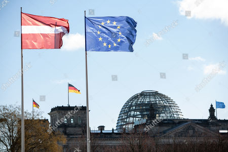 The Latvian national flag (top left) and the German national flag (top right) wave in the wind as the German parliament the Bundestag seen in the background, prior to a meeting between German Chancellor Angela Merkel and the President of Latvia Raimonds Vejonis (both not pictured) at the Chancellery, in Berlin, Germany, 22 February 2019. Vejonis is on an official visit to Germany.