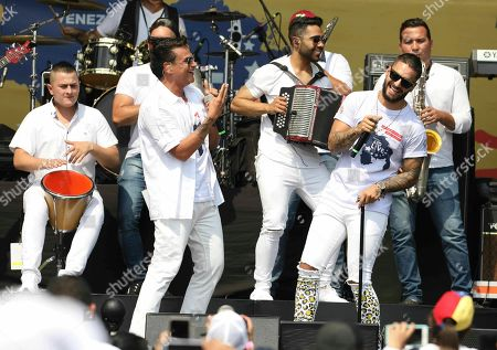 Colombian singers Silvestre Dangond, left, and Maluma sing during the Venezuela Aid Live concert on the Colombian side of Tienditas International Bridge near Cucuta, Colombia, on the border with Venezuela