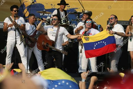 "Gusi, Santiago Cruz, Carlos Vives. Gusi, left center, and Santiago Cruz, hold a Venezuelan national flag as they perform with Carlos Vives at the ""Live Aid Venezuela"" concert at the Tienditas International Bridge on the outskirts of Cucuta, Colombia, on the border with Venezuela. British billionaire Richard Branson organized the mega concert, which features dozens of Latin musicians performing on a giant stage on one side of what Colombian authorities have renamed the ""Unity"" bridge"