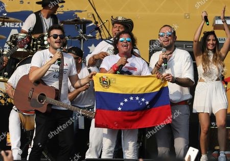"Gusi, Carlos Vives, Santiago Cruz. Gusi, from left, Carlos Vives and Santiago Cruz, hold a Venezuelan national flag as they perform at the ""Live Aid Venezuela"" concert at the Tienditas International Bridge on the outskirts of Cucuta, Colombia, on the border with Venezuela. British billionaire Richard Branson organized the mega concert, which features dozens of Latin musicians performing on a giant stage on one side of what Colombian authorities have renamed the ""Unity"" bridge"
