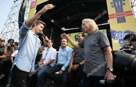 Venezuelan singer Carlos Baute, left, gets ready to embrace Venezuela Aid Live concert organizer Sir Richard Branson, prior to the start of the concert on the Colombian side of the Tienditas International Bridge on the outskirts of Cucuta, Colombia, on the border with Venezuela, . Venezuela's power struggle is set to convert into a battle of the bands Friday when musicians demanding Nicolas Maduro allow in humanitarian aid and those supporting the embattled leader's refusal sing in rival concerts being held at both sides of a border bridge where tons of donated food and medicine are being stored