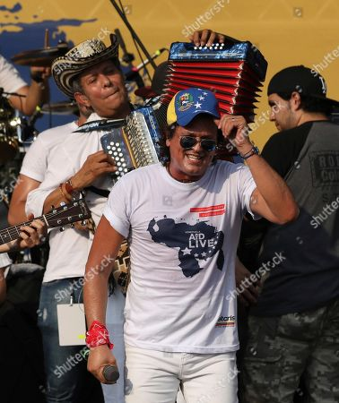 "Egidio Cuadrado, Carlos Vives. Accordion player Egidio Cuadrado and Carlos Vives perform at the ""Live Aid Venezuela"" concert at the Tienditas International Bridge on the outskirts of Cucuta, Colombia, on the border with Venezuela. British billionaire Richard Branson organized the mega concert, which features dozens of Latin musicians performing on a giant stage on one side of what Colombian authorities have renamed the ""Unity"" bridge"