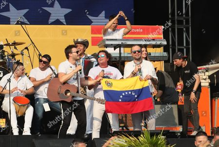 Colombian singers (L-R) Gusi, Carlos Vives and Santiago Cruz perform during the Aid Live concert, funded by British billionaire Richard Branson, at the Tienditas border bridge in Cucuta, Colombia, 22 February 2019.