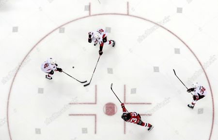 New Jersey Devils left wing Jesper Bratt (63), of Sweden, takes a shot as Ottawa Senators defenseman Cody Ceci (5), defenseman Dylan DeMelo (2) and center Colin White (36) during the second period of an NHL hockey game, in Newark, N.J. The Devils won 4-0