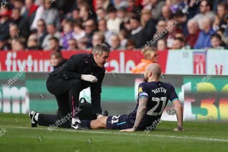 Alan Hutton of Aston Villa receives treatment on the side of the pitch