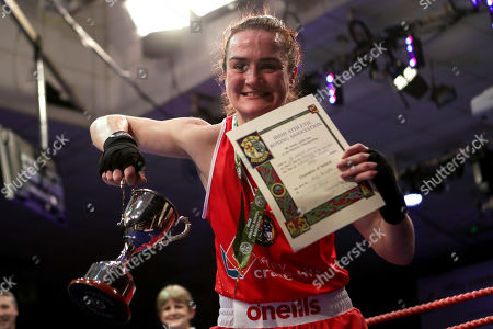 Stock Photo of 60kg ñ Women's Lightweight. Kelly Harrington (red) vs Jelena Jelic (blue). Kelly Harrington celebrates with the trophy