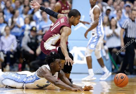 Nassir Little, David Nichols. North Carolina's Nassir Little, bottom, dives while chasing the ball with Florida State's David Nichols (11) during the second half of an NCAA college basketball game in Chapel Hill, N.C