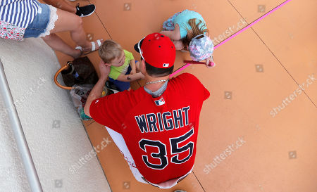 Stock Photo of Boston Red Sox pitcher Steven Wright (35) greets his children Ella, 6, and Lucas, 3, left, before a spring training baseball game against the New York Yankees in Fort Myers, Fla