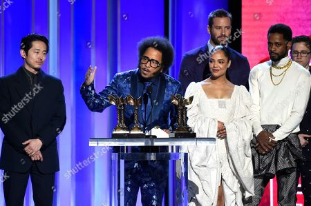 """Steven Yeun, Boots Riley, Tessa Thompson, Armie Hammer, LaKeith Stanfield. Boots Riley, center, accepts the award for best first feature for """"Sorry To Bother You"""" as Steven Yeun, left, Tessa Thompson, right, Armie Hammer and LaKeith Stanfield look on at the 34th Film Independent Spirit Awards, in Santa Monica, Calif"""