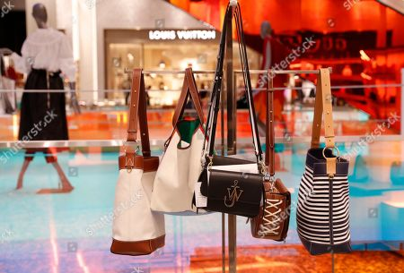Luxury handbags hang from a display inside the Saks Fifth Avenue's flagship Manhattan location in midtown Manhattan, in New York. Saks President Marc Metrick, who has overeseen a what he calls a $250 million redevelopment that aims to reinvent the department store experience to bring theater to luxury shopping at a time when shoppers can buy their designer handbags online