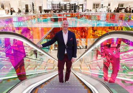 Saks Fifth Avenue President Marc Metrick rides the escalator inside the company's flagship midtown Manhattan store, in New York. A company insider, the 45-year-old Metrick aims to reinvent the department store experience to bring theater to luxury shopping at a time when shoppers can buy their designer handbags online