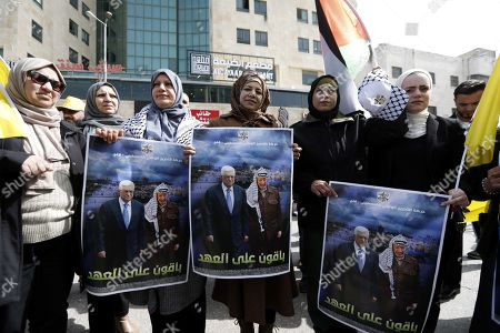 Palestinian protesters hold photos of President Mahmoud Abbas and late leader Yasser Arafat during a protest in solidarity with Abbas in the West Bank city of Hebron, 24 February 2019. Fatah movement and the Palestinian Liberation Organization (PLO) organized the protest against what they call 'US and Israeli acts that aim to undermine the Palestinians authority'.