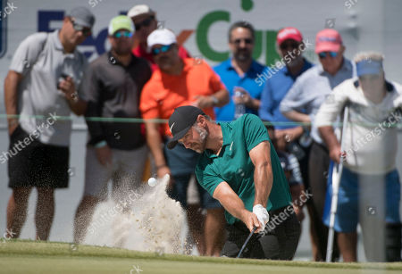 Trevor Immelman of South Africa hits the ball out of the bunker on the 18th hole during the final round of the Puerto Rico Open PGA golf tournament in Rio Grande, Puerto Rico