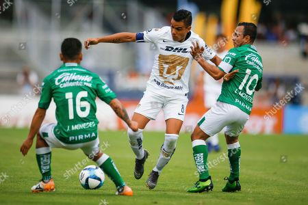 Puma's Pablo Barrera, center, tries to move the ball past Leon's Jean Meneses, left, and Luis Montes during a Mexico soccer league match in Mexico City, . Leon won 3-1