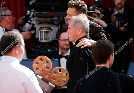Wolfgang Puck, Ryan Seacrest. Ryan Seacrest, left, and Wolfgang Puck arrive at the Oscars, at the Dolby Theatre in Los Angeles
