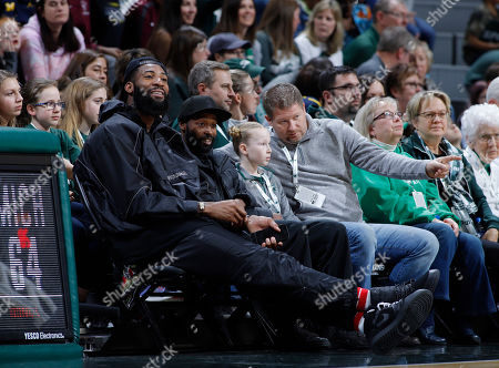 Detroit Pistons center Andre Drummond, left, watches from courtside during an NCAA college basketball game between Michigan and Michigan State, in East Lansing, Mich. Michigan State won 74-64