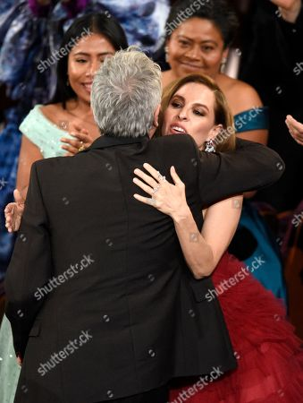 """Marina de Tavira, Alfonso Cuaron. Marina de Tavira, right, congratulates Alfonso Cuaron as he accepts the award for best director for """"Roma"""" at the Oscars, at the Dolby Theatre in Los Angeles"""