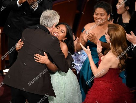 """Alfonso Cuaron, Margarita Martinez Merino, Marina de Tavira. Alfonso Cuaron, left, is congratulated by Yalitza Aparicio, from second left, Margarita Martinez Merino and Marina de Tavirar, as he is announced the winner for best foreign language film for """"Roma"""" at the Oscars, at the Dolby Theatre in Los Angeles"""