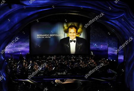 """Gustavo Dudamel conducts the LA Philharmonic performance during the """"In Memoriam"""" at the Oscars, at the Dolby Theatre in Los Angeles as the late writer-director Bernardo Bertolucci is pictured on the screen"""