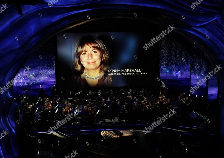 """Gustavo Dudamel, Penny Marshall. Gustavo Dudamel conducts the LA Philharmonic performance during the """"In Memoriam"""" at the Oscars, at the Dolby Theatre in Los Angeles as the late Penny Marshall is pictured on screen"""