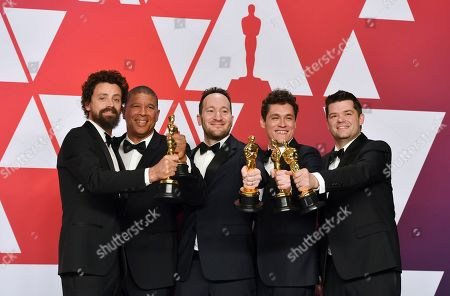 """Bob Persichetti, Peter Ramsey, Rodney Rothman, Phil Lord, Christopher Miller. Bob Persichetti, Peter Ramsey, Rodney Rothman, Phil Lord and Christopher Miller pose with the award for best animated feature film for """"Spider-Man: Into the Spider-Verse"""" in the press room at the Oscars, at the Dolby Theatre in Los Angeles"""