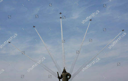 South Korea's Black Eagles aerobatic flight team performs during a rehearsal for the upcoming government ceremony to mark the centennial of the March First Independence Movement Day against Japanese colonial rule (1910-45), in Seoul, South Korea, . The statue, bottom, is Adm. Yi Sun-sin, the national hero who won a major naval victory over Japan in the 16th century