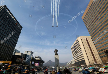 South Korea's Black Eagles aerobatic flight team performs during a rehearsal for the upcoming government ceremony to mark the centennial of the March First Independence Movement Day against Japanese colonial rule (1910-45), in Seoul, South Korea, . The statue, center, is Adm. Yi Sun-sin, the national hero who won a major naval victory over Japan in the 16th century