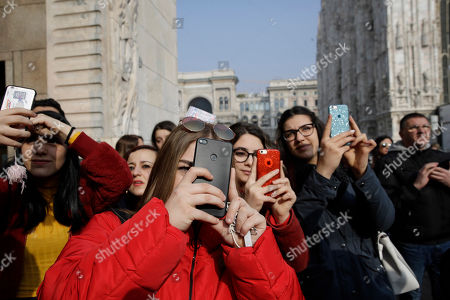 In this picture taken on Tuesday, Feb.19, 2019, young girls shoot video and photos to guests attending the Alberto Zambelli women's Fall-Winter 2019-2020 fashion show, that was presented in Milan, Italy. Fashion is a creative endeavor with no real boundaries, and outside each luxury runway venue, vibrant scenes unfold amid the confluence of influencers, fashion editors, celebrity guests, street photographers and hopeful selfie-snappers