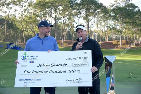 Michael Flaskey, CEO of Diamond Resorts International, right, presents a check to former professional baseball player John Smoltz after the final round of the Tournament of Champions LPGA golf tournament, in Lake Buena Vista, Fla. Eun-Hee Ji won the tournament and Smoltz was the top celebrity finisher