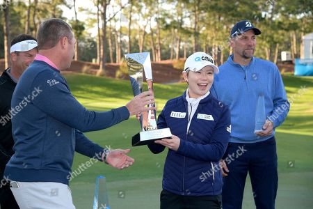 Eun-Hee Ji, of South Korea, is presented the championship trophy after winning the Tournament of Champions LPGA golf tournament, in Lake Buena Vista, Fla. John Smoltz, right, was the top celebrity finisher