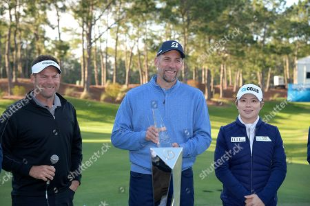 Michael Flaskey, CEO of Diamond Resorts International, left, presents a trophy to John Smoltz, center, for being the top celebrity finisher as winner Eun-Hee Ji, of South Korea, right, watches after the final round of the Tournament of Champions LPGA golf tournament, in Lake Buena Vista, Fla